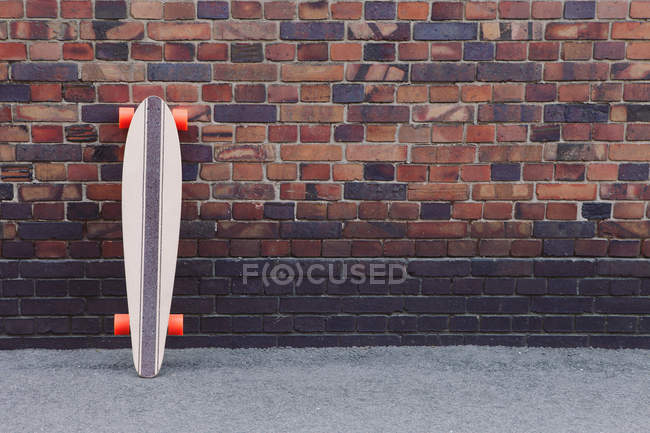 Bricks wall texture and longboard — Stock Photo