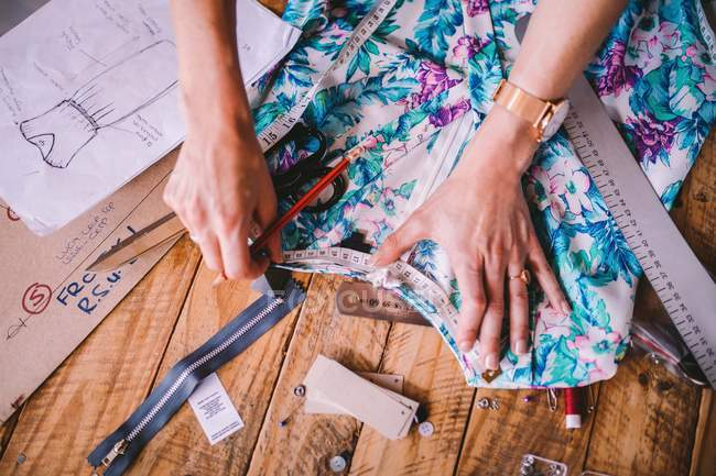 Close-up view of person sewing on table — Stock Photo