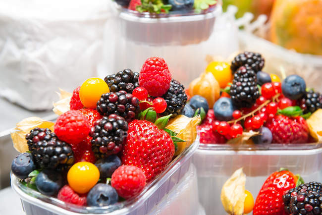 Different berries in plastic boxes — Stock Photo