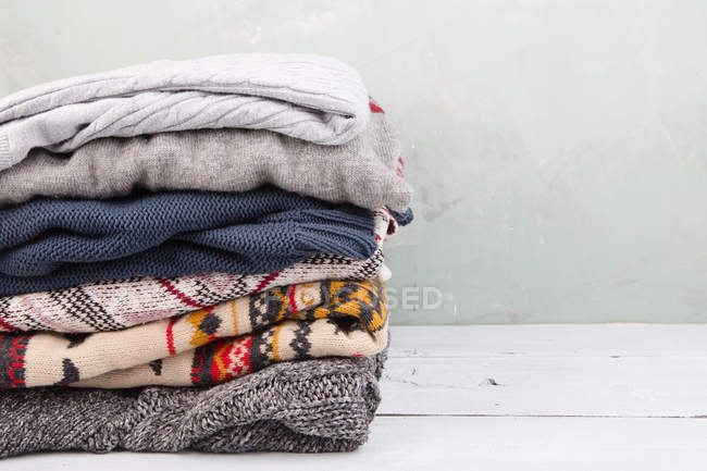 Stack of warm clothing on wooden commode — Stock Photo