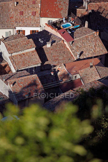 Aerial view of village with houses rooftops, swimming pool on terrace — Stock Photo