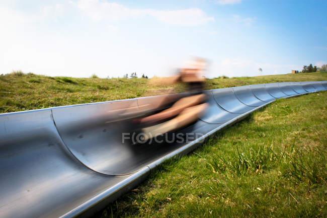 Bewegungsunschärfe Person Rodeln auf einem grünen Hügel — Stockfoto