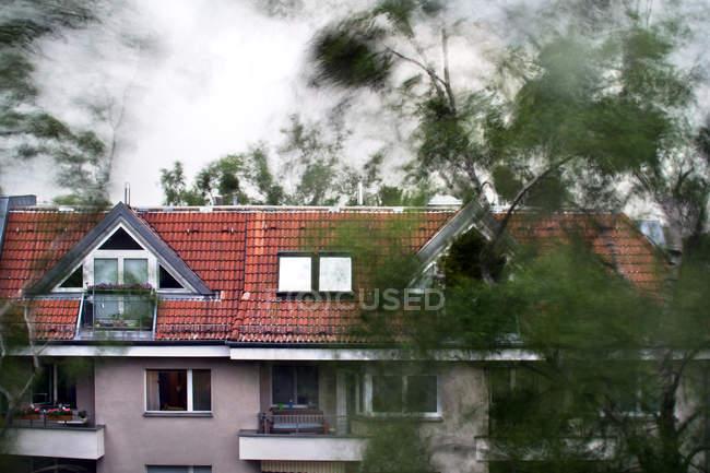 Wohnhaus mit Dachboden Windows auf gefliesten roten Dach, Bäume im Vordergrund — Stockfoto