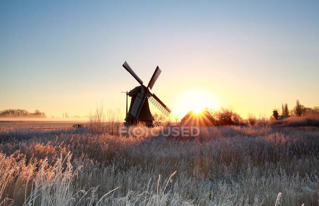 Beautiful sunrise behind windmill in winter — Stock Photo