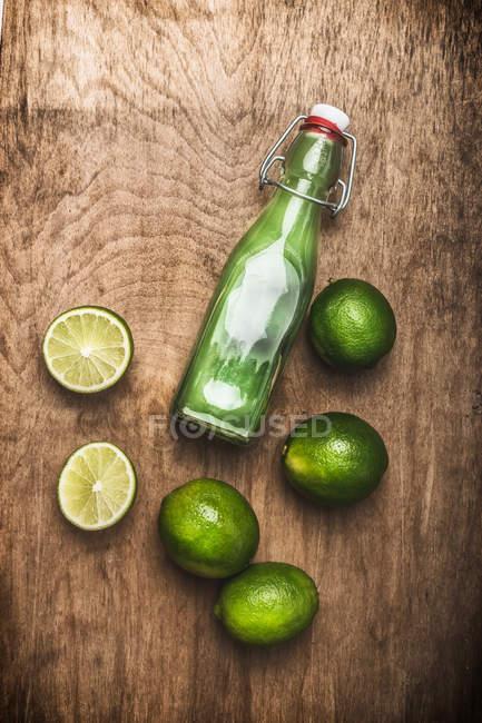 Бутылка с зеленым коктейль и липы — стоковое фото