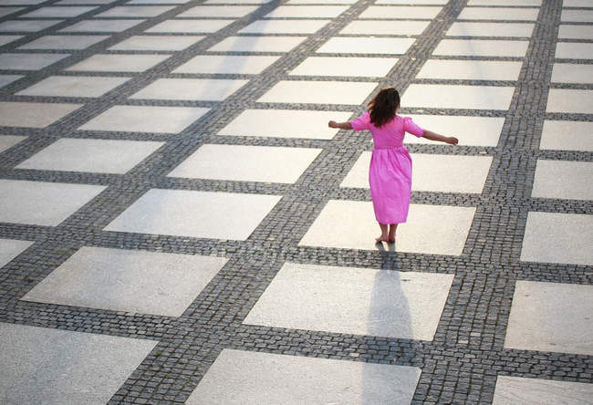 Rear view of girl in pink dress walking on square — Stock Photo