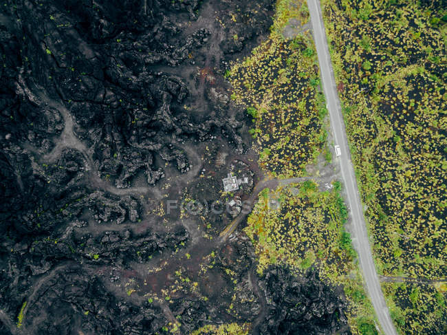 Scenic aerial view of lava field with car on road — Stock Photo