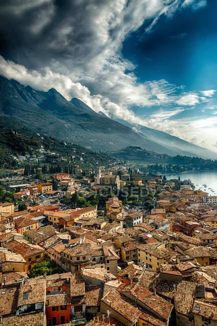 Живописный пейзаж с прибрежный город и горы на озеро Гарда, Италия — стоковое фото