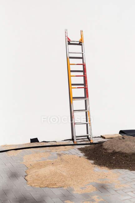 Monte de areia e escada de concreto branco parede no brilho do sol — Fotografia de Stock