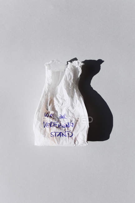 Used crumpled paper bag in light with shadow on background — Stock Photo
