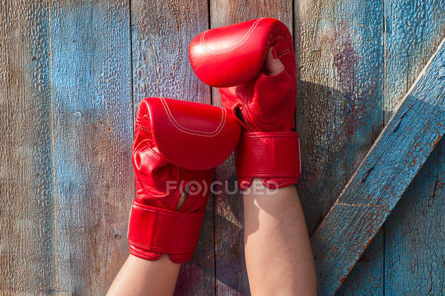 Female hands in red boxing gloves, wooden background — Stock Photo