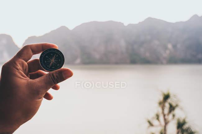Mano con la bussola ed il mare sullo sfondo — Foto stock