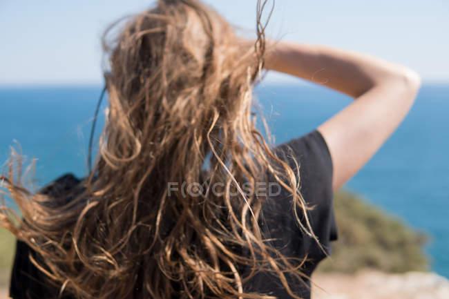 Arrière de la femme à la recherche en mer par temps venteux — Photo de stock
