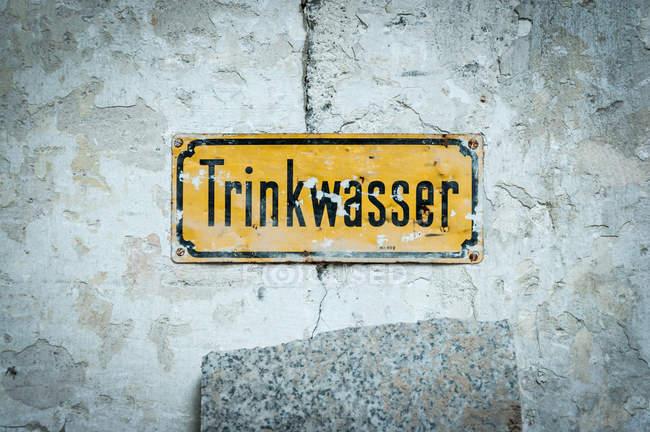 Trinkwasserwald gelbe Namensschild auf schäbige Wand — Stockfoto