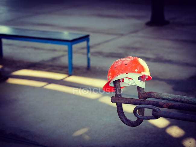 Construction site scene with orange safety helmet hanging on metal construction — Stock Photo