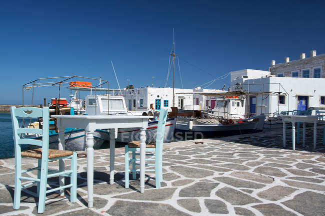 City harbor with moored yachts and street cafe in sunlight, Cyclades, Greece — Stock Photo