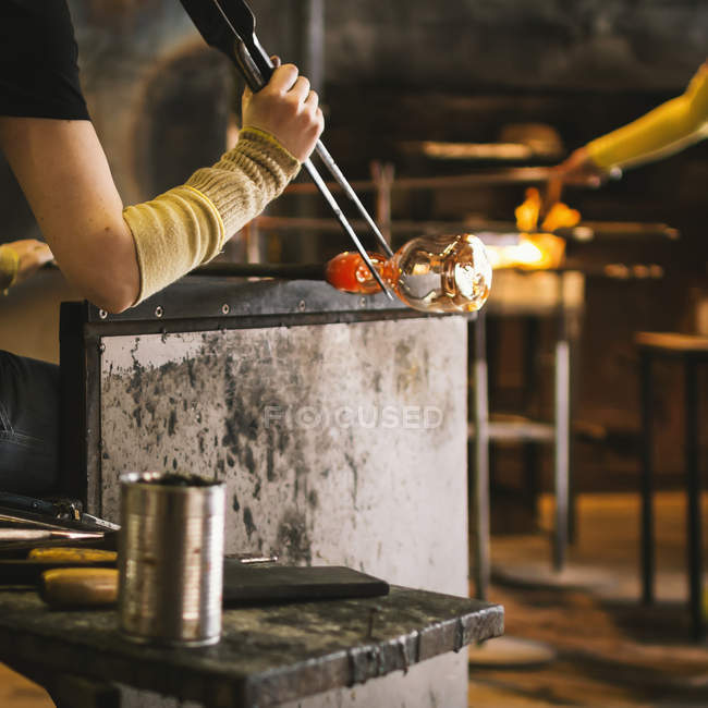 Glass blower working in workshop with melting glassware — Stock Photo