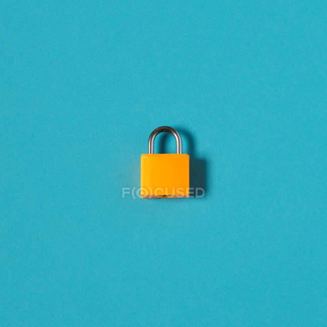 Yellow padlock isolated on blue surface — Stock Photo