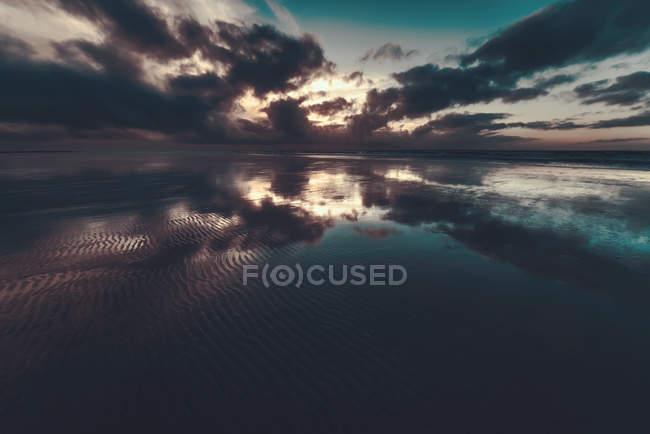 Coucher de soleil à la mer avec ciel nuageux — Photo de stock