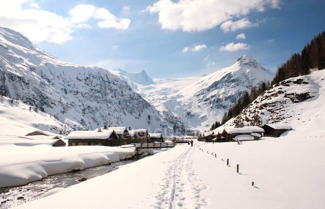 Verschneite Berge und Holzhütten — Stockfoto