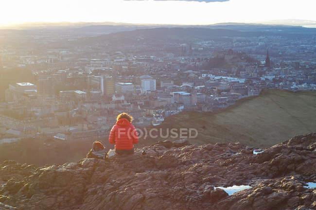 Mulher do viajante no casaco vermelho, sentado no topo da montanha rochosa — Fotografia de Stock