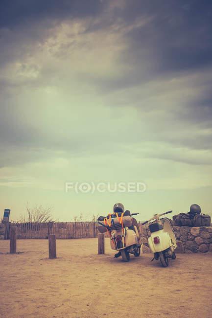 Dos motos con maletas aparcadas por la valla de madera, viajes concepto - foto de stock