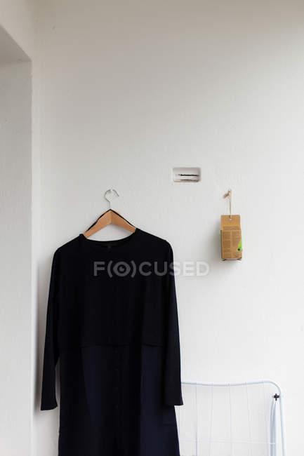 Graue Wand mit Kleiderbügel und Schwarzes Kleid — Stockfoto