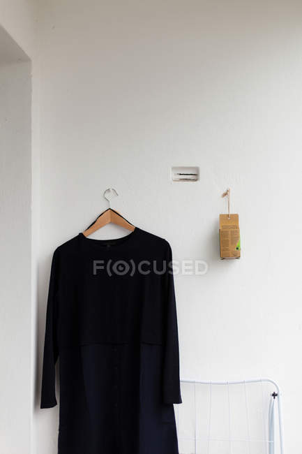 Grey wall with cloth hanger and black dress — Stock Photo