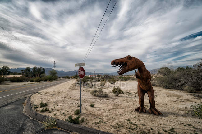 Desert landscape with highway road and iron dinosaur sculpture — Stock Photo