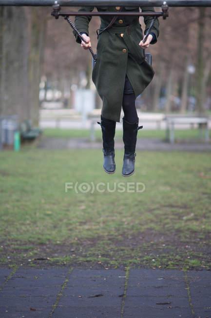 Vue partielle de la fille sur la balançoire dans le parc — Photo de stock