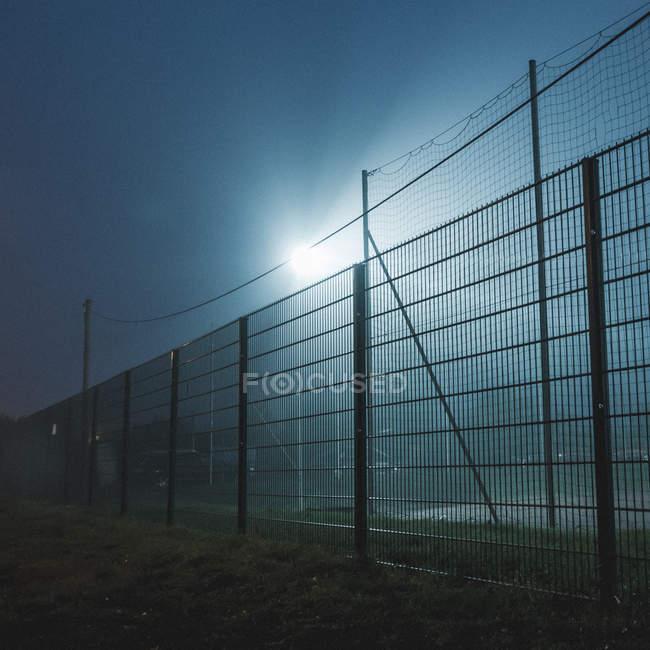 Campo de fútbol detrás de red valla iluminada en la noche - foto de stock
