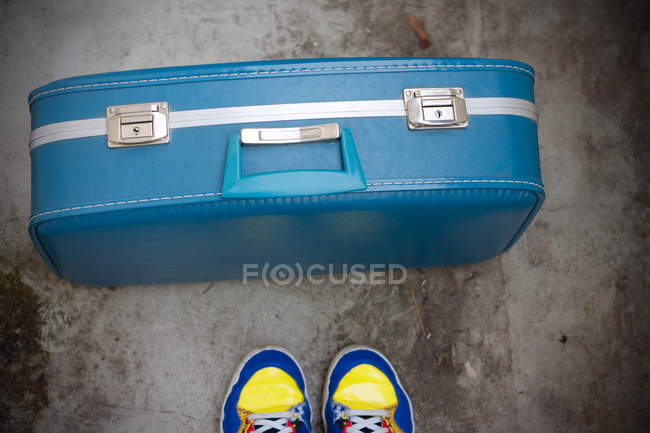 Ritagliate la vista dei piedi di persona in scarpe da ginnastica con la valigia blu — Foto stock