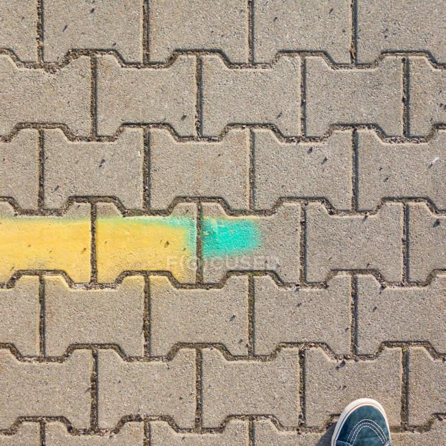 Vista do close-up do pé de pessoa em pedras de pavimentação — Fotografia de Stock