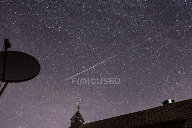 Зоряна ніч небо з літака trail над дахами будинків і супутникова антена — стокове фото