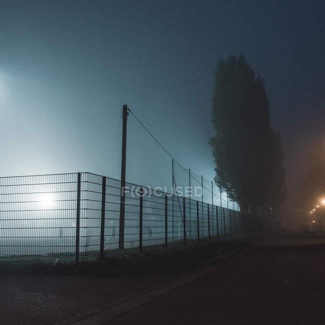 Cancha de fútbol iluminada en vista parcial de noche hay niebla por el callejón de la calle - foto de stock