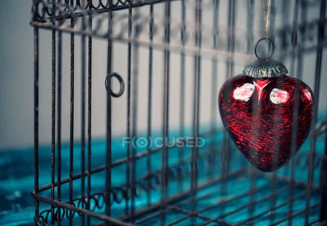 Remise des jouets coeur rouge dans la cage de fer — Photo de stock