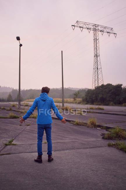 Vue arrière de l'homme en tenue décontractée de ponçage dans les zones rurales — Photo de stock