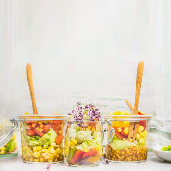 Vegetable salads in jars with greenery — Stock Photo