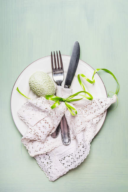 Top view of plate with cutlery on table decorated with easter egg and ribbon - foto de stock