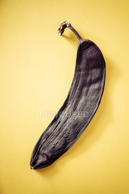Black banana skin on yellow surface — Stock Photo
