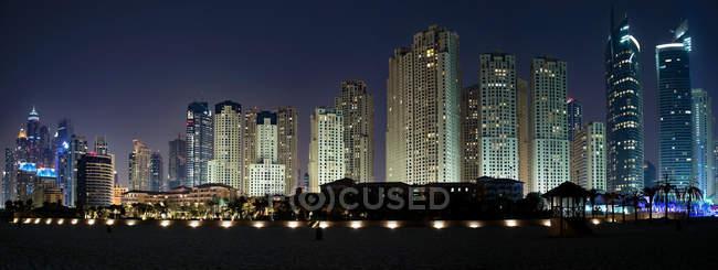 Panorámica paisaje urbano de la metrópoli de Dubai iluminada por la noche, Emiratos Árabes Unidos - foto de stock