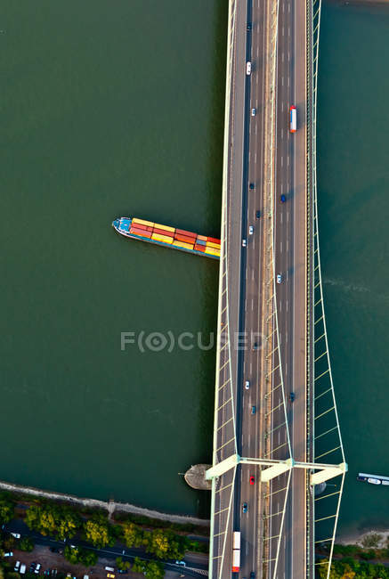 View of a huge cargo ship loaded with containers sailing under bridge with traffic, top view — Stock Photo