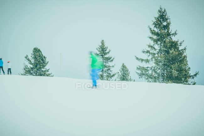 Skifahrer im hellen Verschleiß am Berghang — Stockfoto