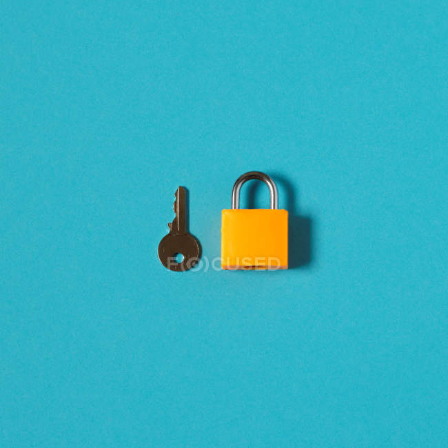Key and yellow padlock isolated on blue surface — Stock Photo