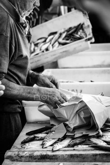 March 13, 2016. Portugal. Cropped view of man preparing plastic bags for fish — Stock Photo