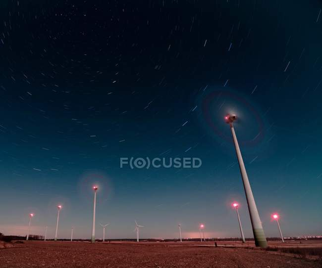 Wind mills producing energy at night — Stock Photo