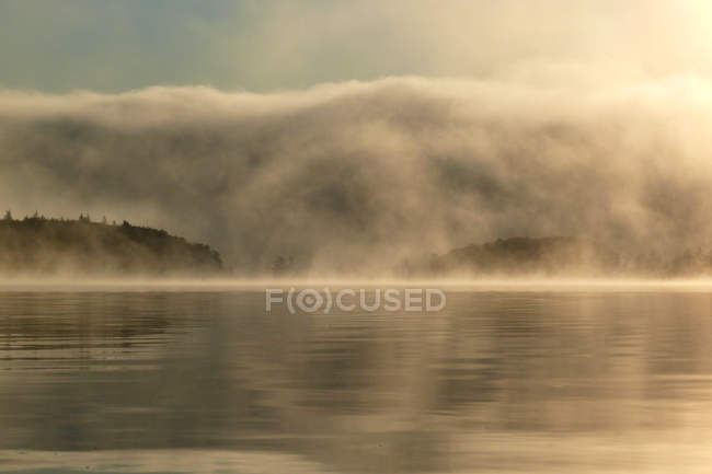 Clouds over lake in foggy weather — Stock Photo