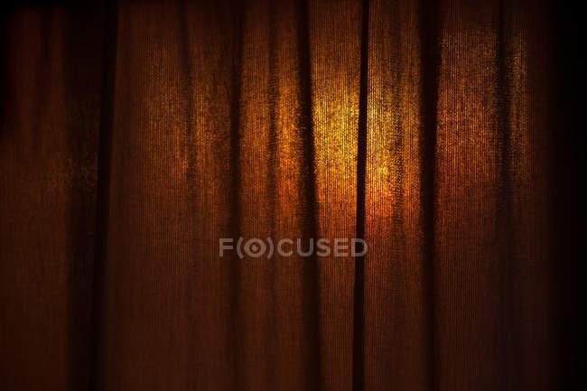 Cortina marrón iluminada con puesta de sol - foto de stock