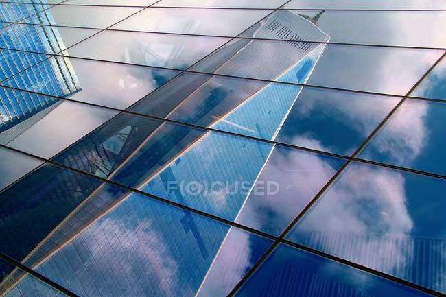 Reflexionando sobre la fachada de vidrio del edificio de rascacielos - foto de stock