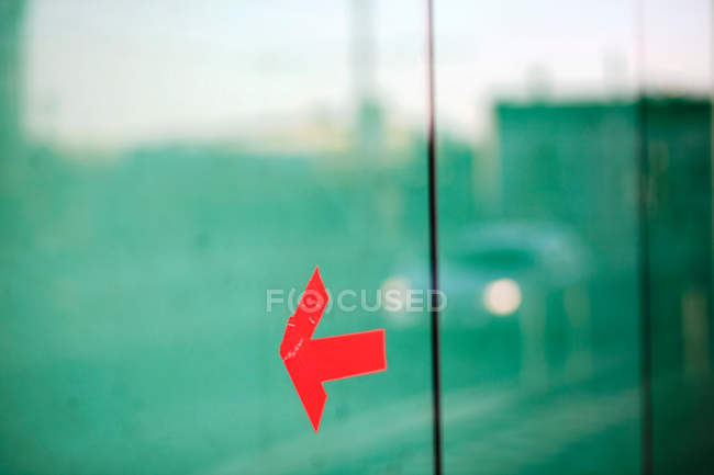 Glass window and red arrow sign — Stock Photo